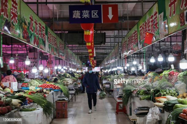 Customer looks at vegetables at a market in Shenyang in China's northeastern Liaoning province on March 10, 2020. - Consumer inflation in China...