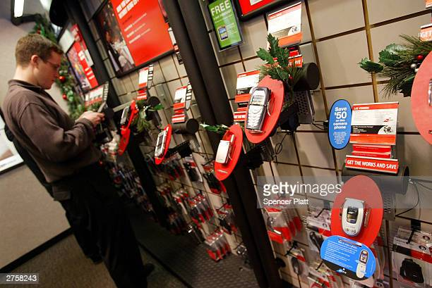 A customer looks at Verizon cell phones on display at a store November 24 2003 in New York City US cell phone customers can now switch carriers...