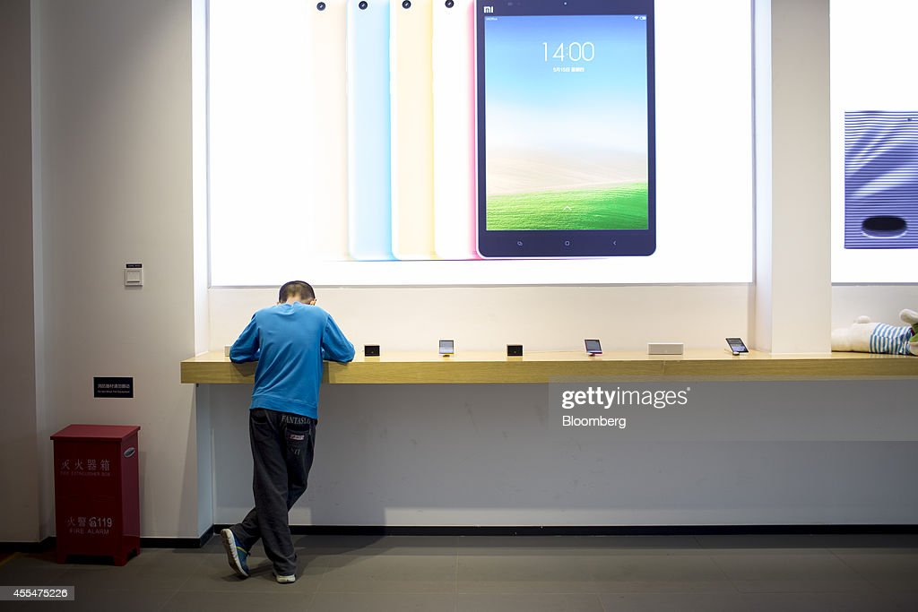 A customer looks at Xiaomi Corp. products at the company's showroom in Beijing, China, on Friday, Sept. 12, 2014. Xiaomi Chief Executive Officer Lei Jun plans to boost global smartphone sales fivefold to 100 million units next year. Photographer: Brent Lewin/Bloomberg via Getty Images