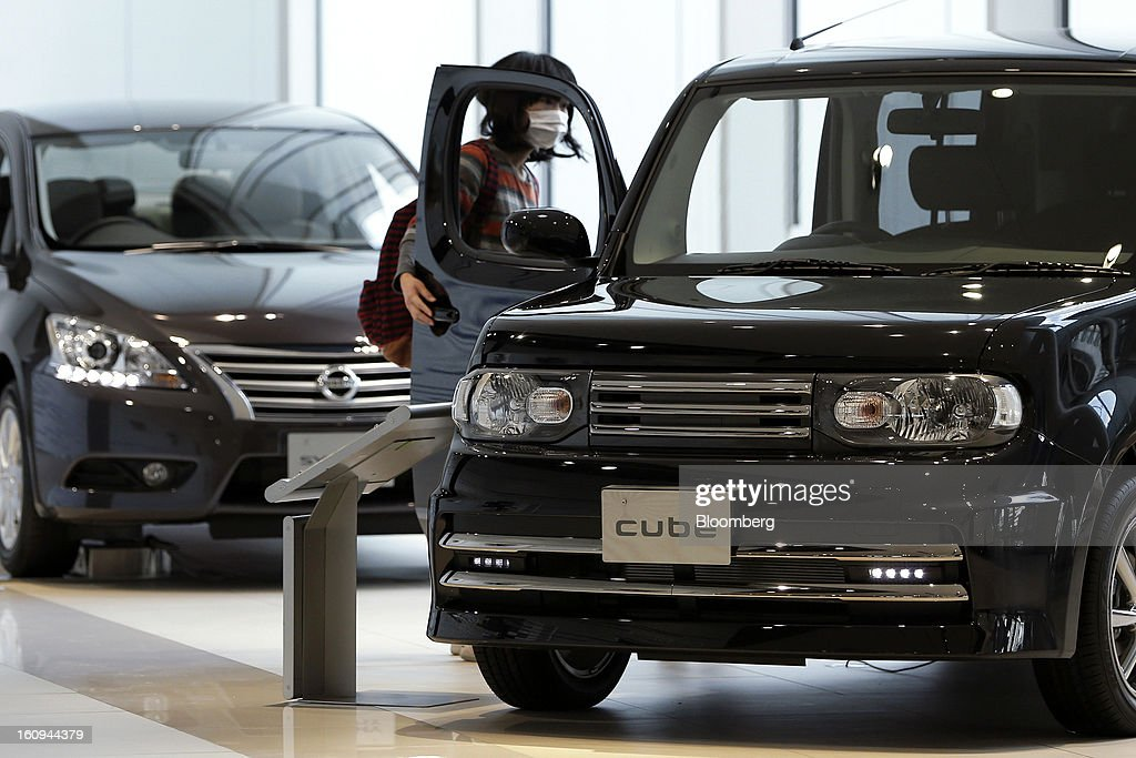 A customer looks inside a Nissan Motor Co. Cube compact vehicle displayed at the company's showroom in Yokohama, Kanagawa Prefecture, Japan, on Friday, Feb. 8, 2013. Nissan, Japan's second-biggest carmaker, reported third-quarter profit that fell short of analysts' estimates, after sales tumbled in China and new models trailed competitors in the U.S. Photographer: Kiyoshi Ota/Bloomberg via Getty Images