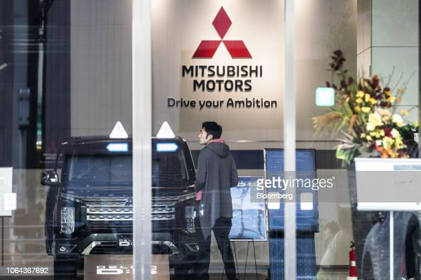 Customer looks inside a showroom at the Mitsubishi Motors Corp. Headquarters in Tokyo, Japan, on Friday, Nov. 23, 2018. Mitsubishi Motors' board...