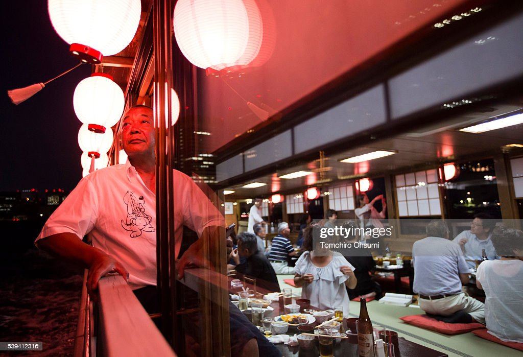 A customer looks out a window of a yakatabune, or traditional low barge style boat, operated by Mikawaya shipping agent, sailing on the Sumida River at night on June 10, 2016 in Tokyo, Japan. About 35 companies operate over 100 yakatabune boats in Tokyo offering services such as dinner or karaoke inside the boats while cruising in Tokyo's bay area, according to the Tokyo Yakatabune Association.