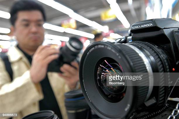 A customer looks over Konica Minolta cameras at a store in Tokyo Thursday May 12 2005