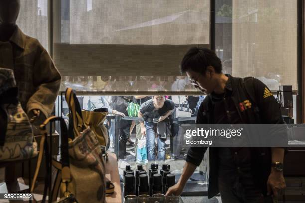 A customer looks through a window while waiting in line at the entrance to the Starbucks Corp Reserve Roastery store in Shanghai China on Friday May...