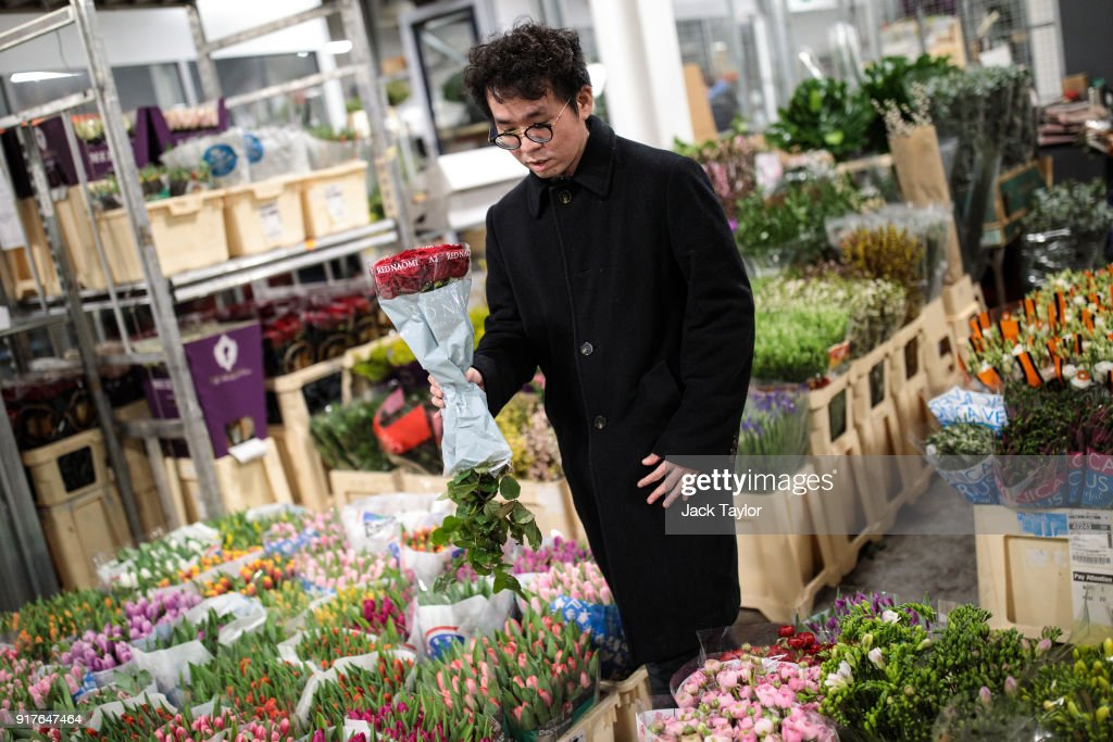 A customer looks through the flowers on display while holding a bunch of roses at New Covent Garden Flower Market ahead of Valentine's Day on February 13, 2018 in London, England. New Covent Garden market is the largest wholesale fruit, vegetable, and flower market in the United Kingdom, supplying 75% of florists in London.