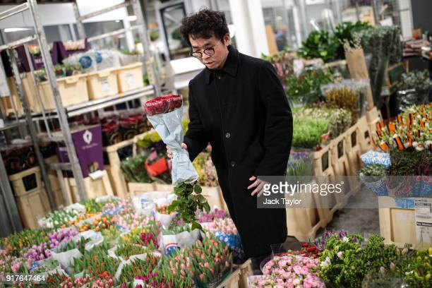 A customer looks through the flowers on display while holding a bunch of roses at New Covent Garden Flower Market ahead of Valentine's Day on...