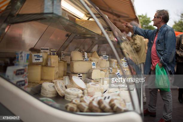 A customer makes a purchase from a cheese stall at an open air market in Nice France on Thursday May 14 2015 The European Commission and the...