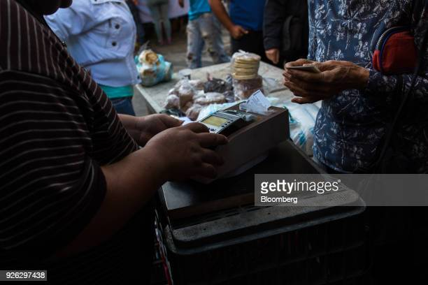 A customer makes a purchase using a debit card at a street vendor in Caracas Venezuela on Thursday March 1 2018 In hyperinflationary Venezuela paper...