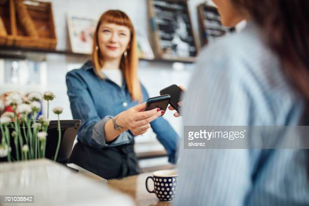 Customer making contactless payment at cafe