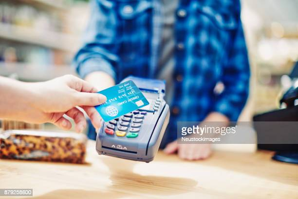 customer making contactless payment through credit card - convenience store counter stock photos and pictures