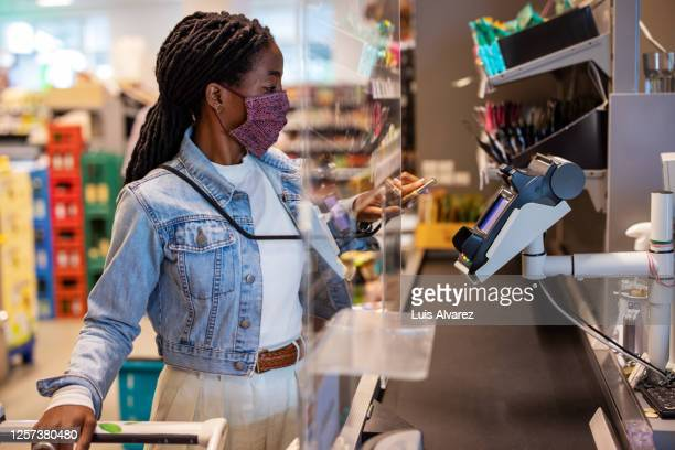 customer making payment with nfc technology at supermarket - black trousers stock pictures, royalty-free photos & images