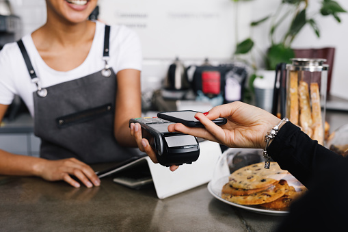 Customer making wireless payment using smartphone in cafe 912442200
