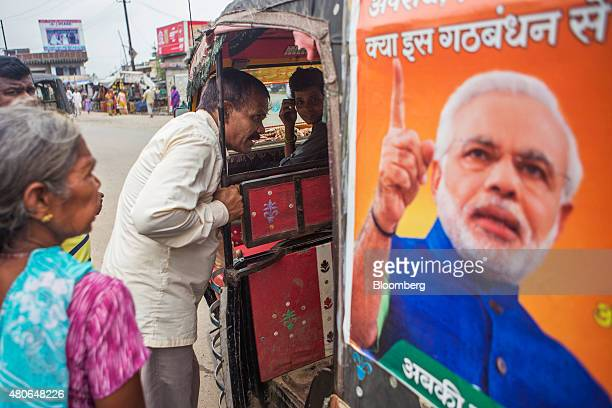 A customer negotiates with the driver of an autorickshaw featuring a poster of Indian Prime Minister Narendra Modi in Patna Bihar India on Saturday...