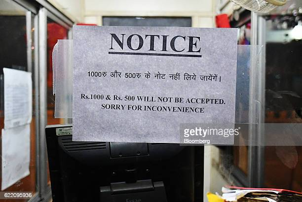 A customer notice advising that Indian five hundred and one thousand rupee banknotes will not be accepted is seen on the window of a parking lot...