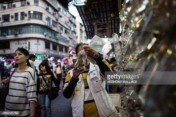 A customer observes the behaviour of a fish before choosing whether to purchase it outside a shop at the Mong Kok Goldfish Market in Hong Kong on...