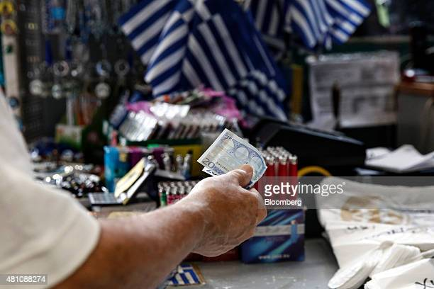 A customer offers a 20 euro note in payment for goods purchased inside a one euro store in Athens Greece on Friday July 17 2015 Germany's Parliament...