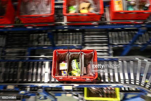 A customer order crate travels along a conveyor belt at the Ocado Group Plc distribution centre in Dordon UK on Friday Dec 16 2016 Ocado provides...
