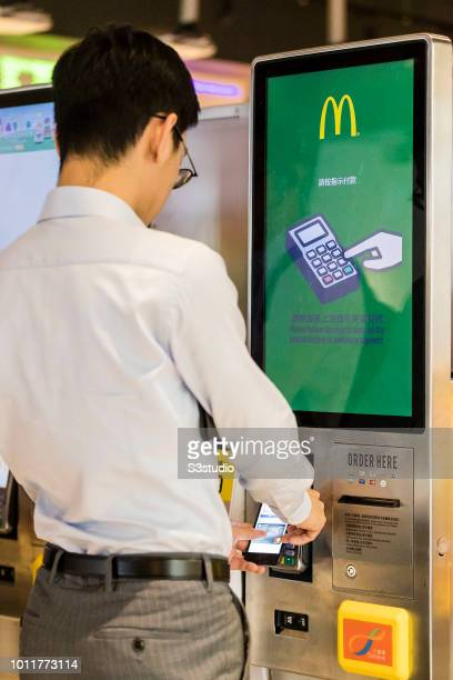 Customer ordering food in automated selfordering kiosk with credit card mobile payment method at a McDonald's fast food restaurant in Hong Kong Hong...