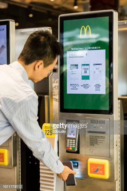 Customer ordering food in automated selfordering kiosk with WeChat Pay HK / Alipay HK mobile payment method at a McDonald's fast food restaurant in...
