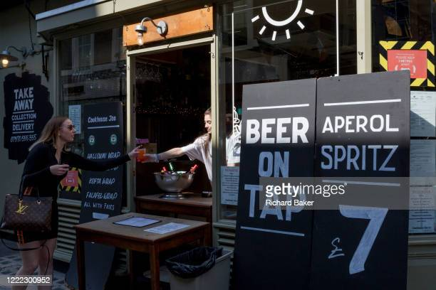 Customer orders a cold drink from a re-opened bar in Soho where beer on tap is available on the day that UK Prime Minster, Boris Johnson announced in...