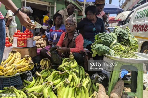 A customer passes a Ghana cedi banknote to a street vendor for the purchase of fresh produce in Accra Ghana on Thursday March 15 2018 Ghana wants to...