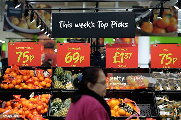 Customer passes a sales display of oranges and pineapples in the fruit and vegetable section of an Asda supermarket, operated by Wal-Mart Stores...
