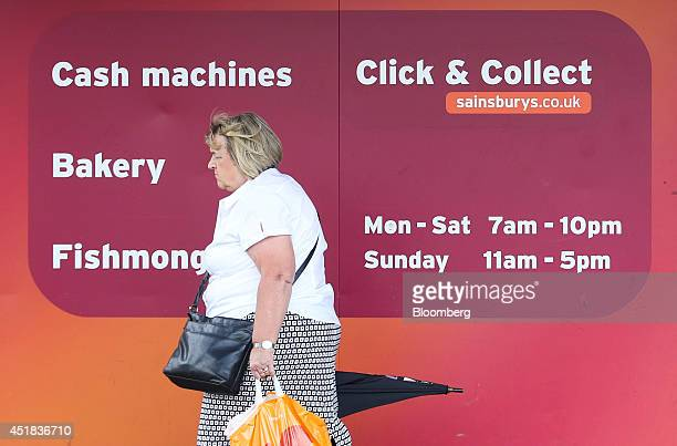 A customer passes a sign advertising Sainsbury's services including banking and 'Click and Collect' outside one of the company's supermarket stores...