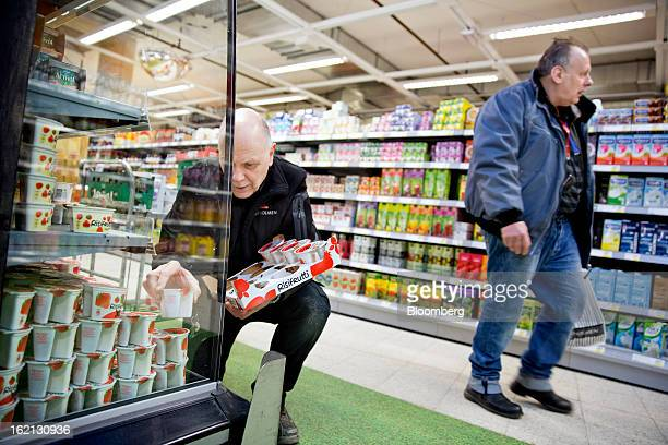 A customer passes an employee as he restocks a chilled display cabinet with dairy products inside an ICA supermarket store in Stockholm Sweden on...