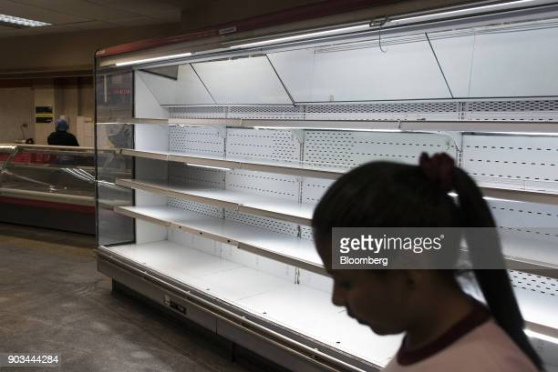 A customer passes empty shelves at a grocery store in Caracas Venezuela on Tuesday Jan 9 2018 Hordes of desperate shoppers emptied supermarkets and...