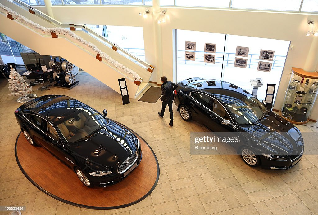 A customer passes two Jaguar XJ series automobiles on display in an independent auto showroom in Moscow, Russia, on Friday, Dec. 28, 2012. Tata Motors Ltd.'s Jaguar Land Rover luxury unit signed a letter of intent with Saudi Arabia's government to study the feasibility of setting up a factory to build its models locally. Photographer: Andrey Rudakov/Bloomberg via Getty Images