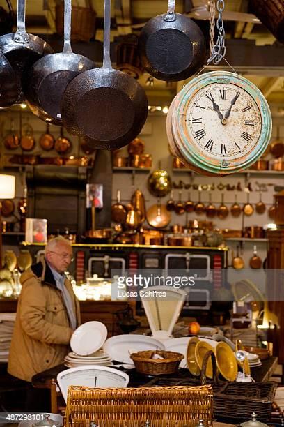 Customer PaulHenri Goumet browses antique dealer Francois Bachelier's store specialised in antique kitchen ustensils in SaintOuen flea market on...