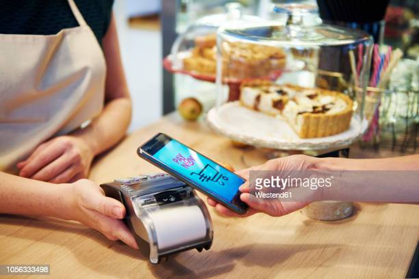 customer paying cashless with smartphone in a cafe - convenience stock photos and pictures