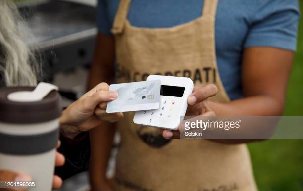 customer paying for coffee at bicycle coffee shop - contactless payment stock pictures, royalty-free photos & images