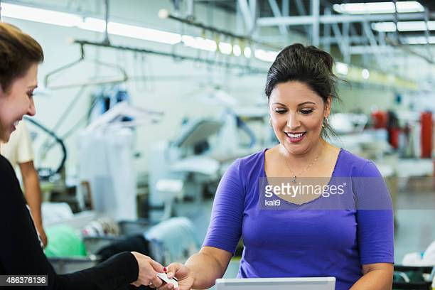 customer paying for dry cleaning handing card to cashier - dry cleaner stock pictures, royalty-free photos & images