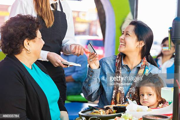 customer paying for meal at tex-mex restaurant with credit card - grandma invoice stock pictures, royalty-free photos & images
