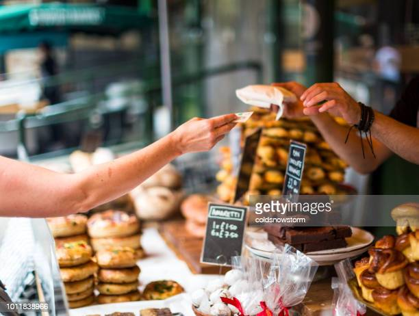 customer paying for sweet pastry using cash at food market - british pound sterling note stock pictures, royalty-free photos & images
