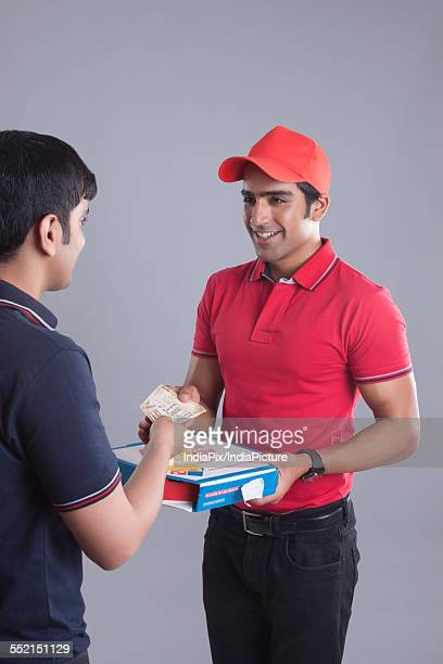 Customer paying pizza delivery man over gray background
