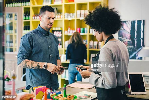 Customer paying through credit card while looking at barista using card reader in cafe