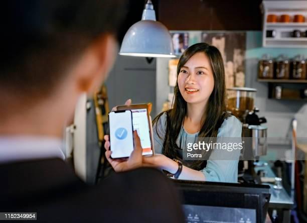 kunden zahlen über digitale geldbörse im café - strichkodeleser stock-fotos und bilder