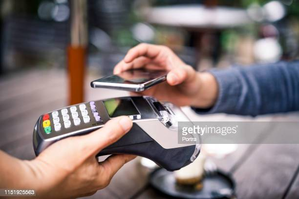 customer paying using mobile payment to cafe owner - contactless payment stock pictures, royalty-free photos & images