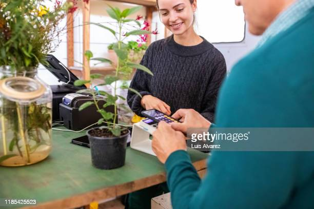 customer paying via nfc technology at garden center - nfc stock pictures, royalty-free photos & images