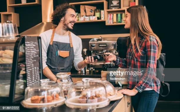 Customer paying via smart phoone at a coffee shop