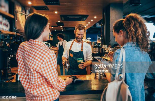 customer paying while getting her order - lining up stock pictures, royalty-free photos & images
