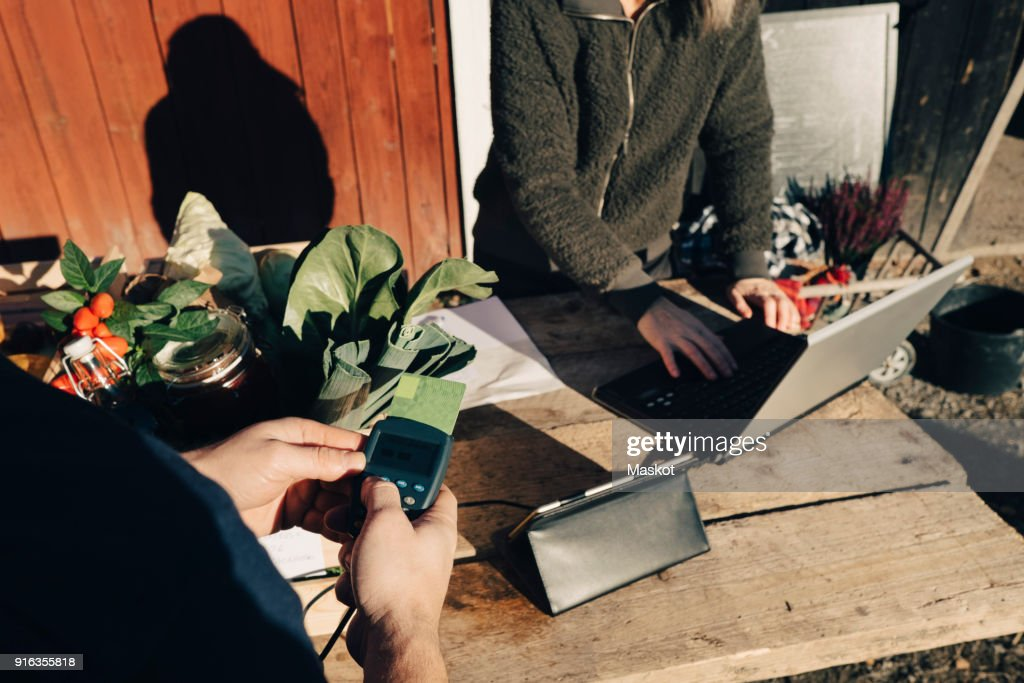 Customer paying with credit card while farmer using laptop at market : Stock Photo