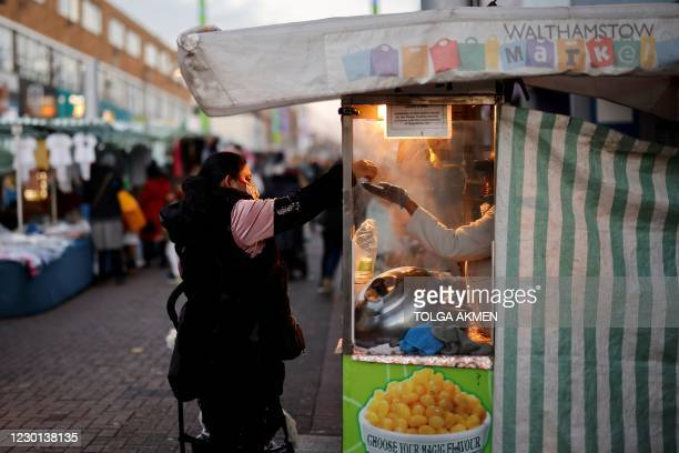 Customer pays a trader for take-away food in Walthamstow Market in Waltham Forest in East London on December 15, 2020 ahead of fresh measures for the...
