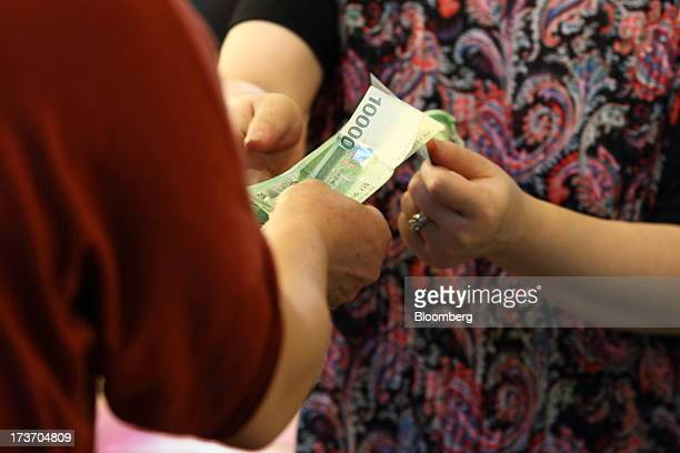 Customer pays a vendor for her purchases at Noeun Agricultural and Marine Products Wholesale Market in Daejeon, South Korea, on Tuesday, July 16,...