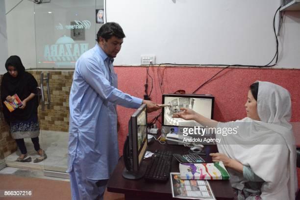 A customer pays after eating at Balochistan's first women run restaurant in Quetta Pakistan on October 25 2017 Hamida Ali Hazara owner of...