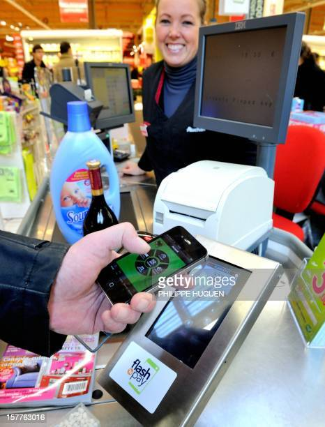 A customer pays at a register with a smartphone application on December 6 2012 in a Auchan supermarket in FachesThumesnil near Lille northern France...