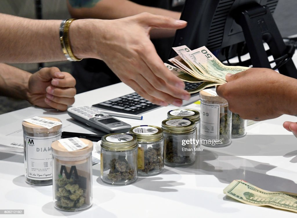 A customer pays for cannabis products at Essence Vegas Cannabis Dispensary after the start of recreational marijuana sales began on July 1, 2017 in Las Vegas, Nevada. Nevada joins seven other states allowing recreational marijuana use and becomes the first of four states that voted to legalize recreational sales in November's election to allow dispensaries to sell cannabis for recreational use to anyone over 21.