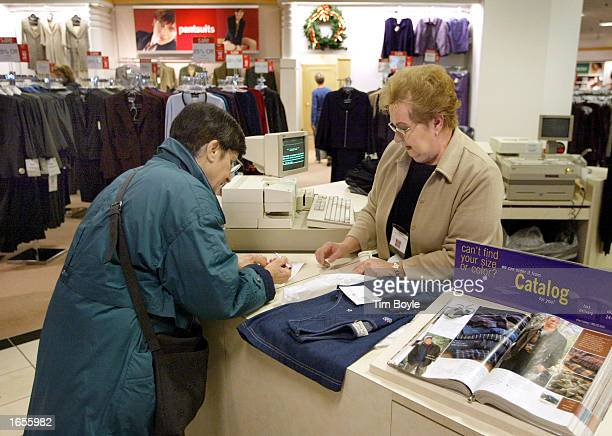 A customer pays for her purchases at a checkout kiosk November 22 2002 at a JC Penney store at Woodfield Mall in Schaumburg Illinois JC Penney...